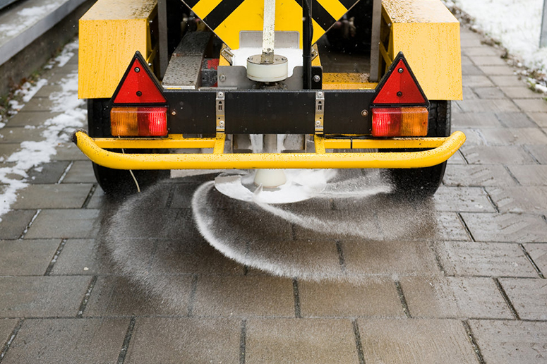 v-box salt machine spreading salt on sidewalk