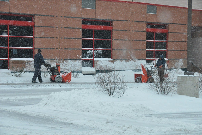 snow management crews using snowblowers on sidewalks